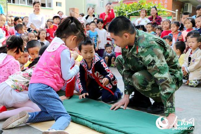 人民网钦州5月1日电 在五一劳动节到来之际,4月27日,广西海警第三支队的官兵走进钦州市第二幼儿园,与孩子们进行了交流互动,从小培养孩子们的爱国意识。 上午8时30分,海警官兵们出现在该幼儿园,在校师生非常激动。9时整,海警官兵与孩子们一同开始升国旗仪式。随着出旗的一声口令,小朋友们在海警官兵的带领下,踏着整齐的步伐,护着五星红旗走向升旗台交给海警官兵。理旗、护旗、交旗、升旗、敬礼.