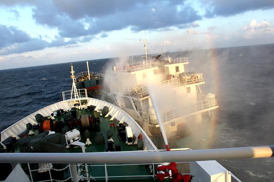 中国海警舰船在辖区海域追击非法走私成品油船,使用水炮压制涉案船舶。