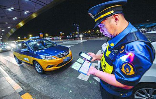 执法人员正在对出租车驾驶员信息进行核查