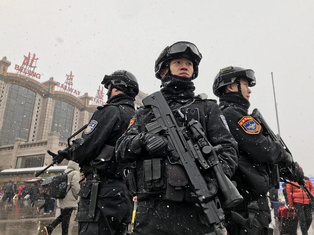 北京:旅客春运返程 特警冒雪执勤
